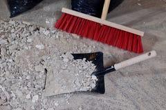 Kvast och sopskyffel på en hög av konstruktionsspillror Arkivfoton
