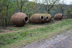 Kvevri, jarros da argila para o winemaking perto da cerca Imagens de Stock