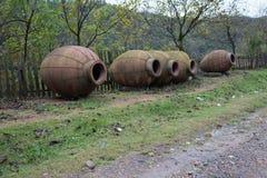 Kvevri leratillbringare för winemaking nära staketet Arkivbilder