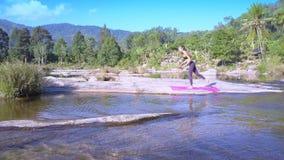 Kvinnaändringsyoga poserar på benet bland floden arkivfilmer