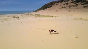 Kvinnaändringsyoga poserar på sand vid flyg- sikt för havet lager videofilmer