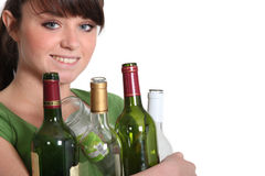 Kvinnaåtervinningglasflaskor Arkivfoto