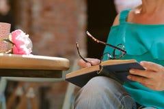 Kvinnaöppning och läsning en bok med kaffekoppen på trätabellen i tappningkafé royaltyfri bild