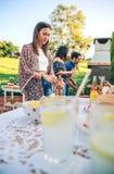 Kvinnaöppningsölflaska i sommargrillfest arkivfoton