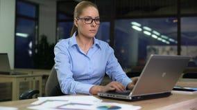 Kvinnaöppningsbärbar dator som startar nattförskjutningen, motiverad anställd som på övertid arbetar arkivfilmer