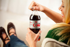 Kvinnaöppningsflaskan av Diet Coke producerade vid cocaen - colakomp Royaltyfri Foto