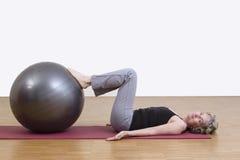 Kvinnaövningar med pilatesbollen Arkivfoto