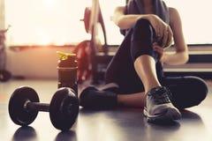 Kvinnaövningsgenomkörare i idrottshallkondition som bryter för att koppla av att rymma äpplefrukt, når utbildning av sporten royaltyfri foto