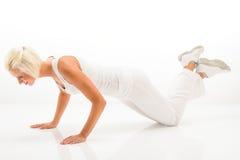 Kvinnaövningspushup på den vita konditiondräkten Royaltyfria Foton