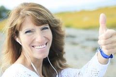 Kvinna 60 år gammal headphonerealitet Fotografering för Bildbyråer