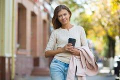Kvinna 30 år gammalt gå i staden på en solig dag med en kopp arkivfoto