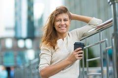 Kvinna 30 år gammalt gå i staden på en solig dag med en kopp royaltyfria bilder