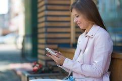 Kvinna 30 år gammalt gå i staden på en solig dag med en sma arkivfoto