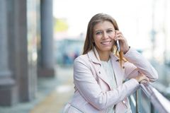 Kvinna 30 år gammalt gå i staden på en solig dag med en sma royaltyfri fotografi