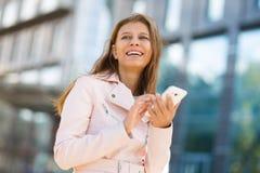 Kvinna 30 år gammalt gå i staden på en solig dag med en sma fotografering för bildbyråer