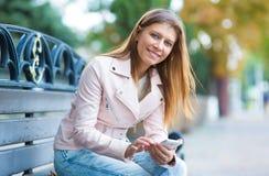 Kvinna 30 år gammalt gå i staden på en solig dag med en sma royaltyfri foto