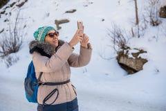 Kvinna 50 år gammalt tagande foto i bergen i vinter, Alma Fotografering för Bildbyråer