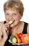 Kvinna (67 gammala år) som äter grönsaker Royaltyfri Bild