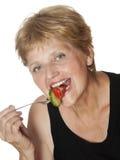 Kvinna (67 gammala år) som äter grönsaker från gaffel Arkivfoto