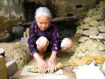 Kvinna av den Quao krukmakeribyn som knådar jord för keramisk lera Arkivbild