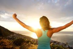 Kvinna bakifrån som ut sträcker armar vid soluppgång Arkivbilder