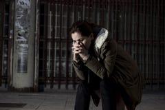Kvinna bara i gatalidandefördjupningen som ser ledset desperat och hjälplöst sammanträde som är ensamt i smutsig mörk stads- bakg Arkivfoton