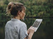 Kvinna bara i natur genom att använda ett digitalt minnestavlainternetuppkoppling- och loppbegrepp arkivbild