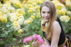 Kvinna bara och många gula rosor omkring Arkivbild