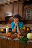 Kvinna bland grönsakerna i köket Arkivfoto