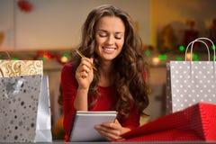Kvinna bland kontrollerande lista för shoppingpåsar i julkök Arkivfoto