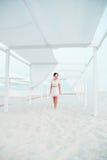 Kvinna brunett med kort hår i den vita klänningen på stranden av havet, hav nära solskugga, tält semester Royaltyfri Fotografi