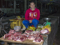 Kvinna bucher som säljer kött på marknaden Arkivfoto