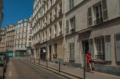 Kvinna, byggnader och blå himmel på gatan av Montmartre på Paris Arkivfoton