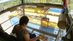 Kvinna Crane Operator Sits, i kabin och att ladda för styrning lager videofilmer