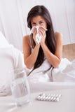 Kvinna dåligt i säng med en förkylning och en influensa Fotografering för Bildbyråer