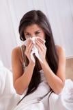 Kvinna dåligt i säng med en förkylning och en influensa Arkivfoto