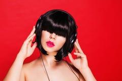 Kvinna dj som lyssnar till musik på hörlurar som tycker om Arkivfoto
