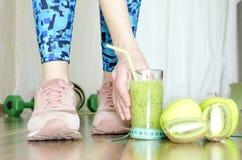 Kvinna efter övningar som dricker den nya gröna smoothien Begrepp av den sunda livsstilen och lossing vikt royaltyfri foto