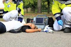 Kvinna efter olycka med person med paramedicinsk utbildning- och defibrillatorförsta hjälpen Arkivbilder