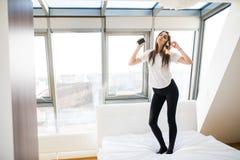 Kvinna eller tonårs- flicka i hörlurar som lyssnar till musik från smartphonen, hemma sjunger och dansar på säng royaltyfria bilder