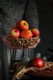kvinna för äpplekorgholding Arkivbild
