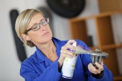 Kvinna för automatisk mekaniker som smörjer automatiskdelen royaltyfri fotografi