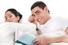 kvinna för avläsning för man för underlagbok lyckligt sova Royaltyfria Foton