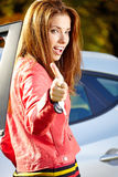 Kvinna för bilchaufför som visar nya biltangenter och bilen. Royaltyfria Foton