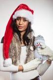Kvinna för blandat lopp i den santa hatten med den lilla snögubben Arkivbild
