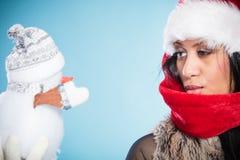 Kvinna för blandat lopp i den santa hatten med den lilla snögubben Arkivbilder