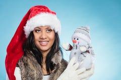 Kvinna för blandat lopp i den santa hatten med den lilla snögubben Fotografering för Bildbyråer