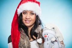 Kvinna för blandat lopp i den santa hatten med den lilla snögubben Royaltyfria Bilder