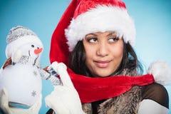 Kvinna för blandat lopp i den santa hatten med den lilla snögubben Arkivfoton
