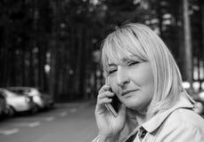 Kvinna för blont hår som talar på mobiltelefonen och att le Royaltyfria Bilder